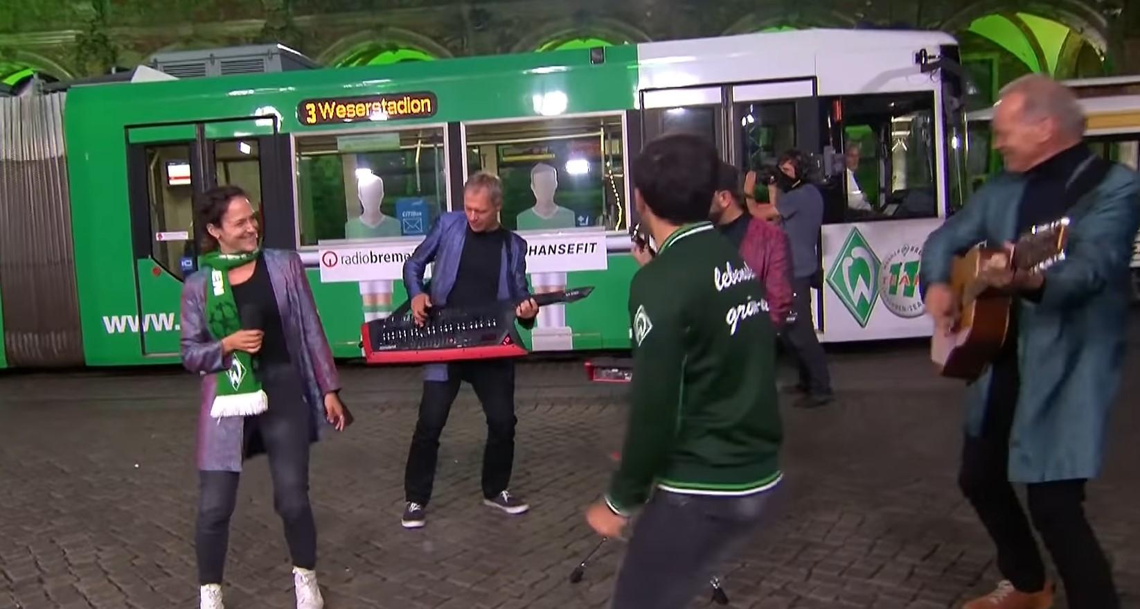 Zollhausboys auf dem Marktplatz, Florian Kohfeldt hört aus der Straßenbahn zu.